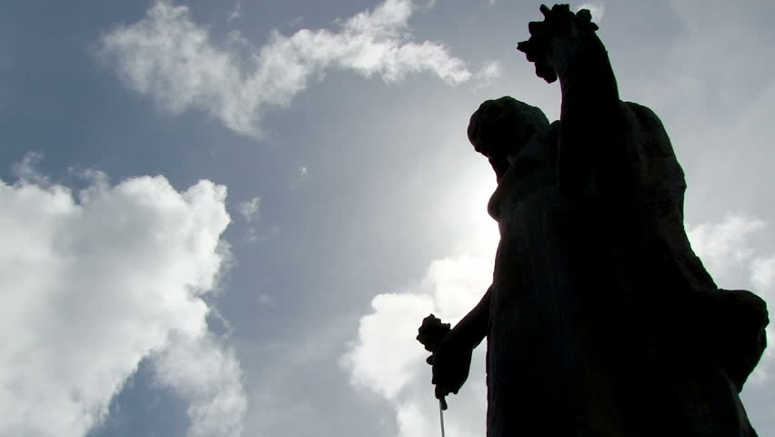 Timelapse of white clouds passing over the silhouette of a statue in Willemstad, Curacao