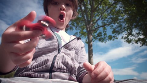4k Child Having Fun Outdoors with Fidget Spinner.