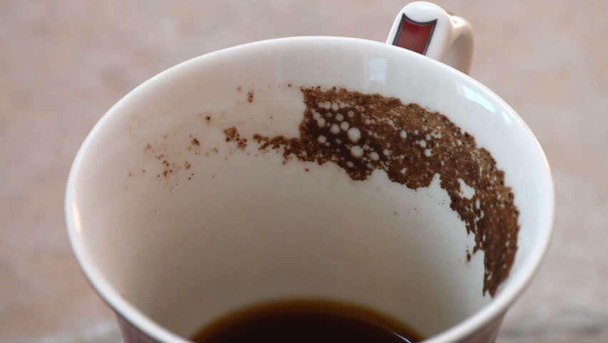 Guessing on the coffee grounds. Coffee mug with coffee grounds rotate .Close-up
