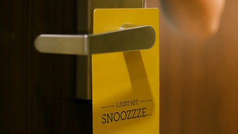 """Clip of a woman's hand removing a yellow Do Not Disturb sign on a hotel door handle and then putting it back again. The words on the sign says """"I just hit snoozzze..."""""""