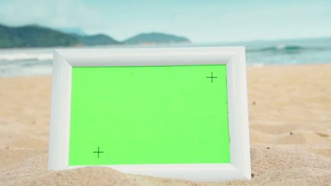 Horizontal white photo frame with green screen and tracking points, for advertising copy space of photos/videos, on a summer beach scene background.