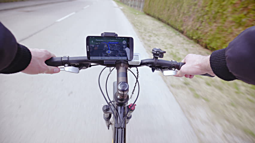 Person POV of bicycle path navigation 4K. First person viewpoint with GPS navigation in focus on handlebar while driving on road.