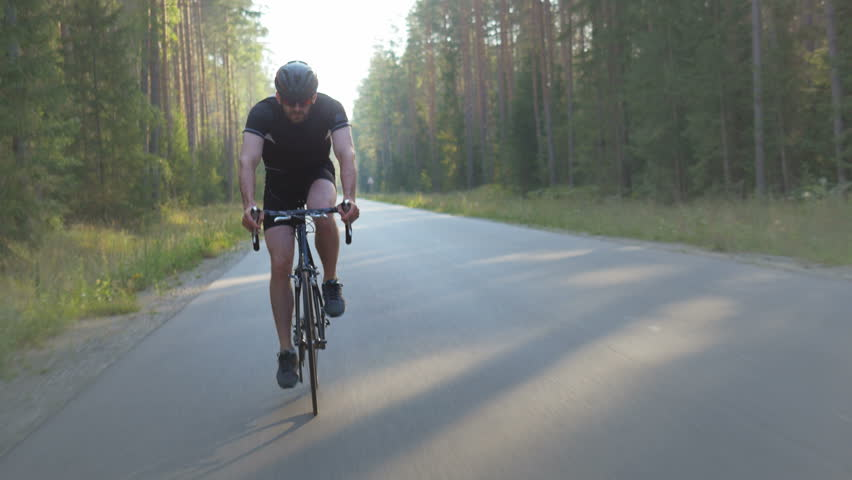 Male Cyclist Doing Endurance Training On An Open Road Professional Triathlon Athlete Riding A Bike