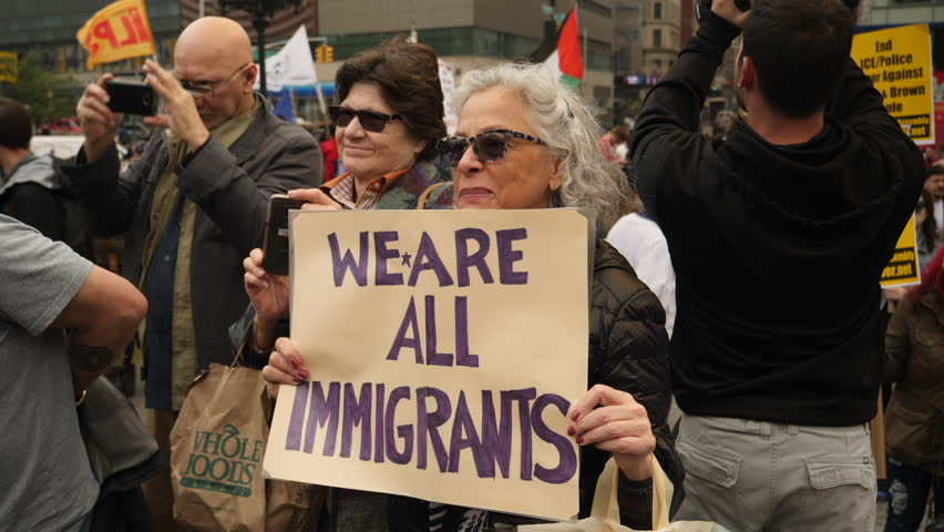 New York City, May 2016. Elder white woman holding 'We Are All Immigrants' sign at protest in New York City.
