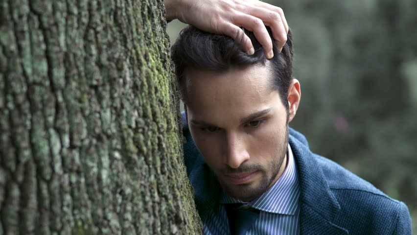 desperate businessman while holding his head leaning on a tree #27214435