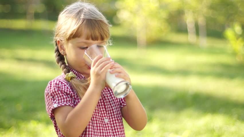 Portrait of smiling girl drinking milk. Milk mustache. Thumbs up. Ok.
