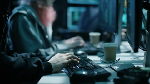 Team of Internationally Wanted Boy and Girl Hackers Organize Advanced Malware Attack on Corporate Servers. Place is Dark and Has Multiple Displays. Shot on RED EPIC-W 8K Helium Cinema Camera.