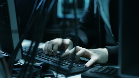 Dangerous Hooded Hacker Breaks into Government Data Servers and Infects Their System with a Virus. His Hideout Place has Dark Atmosphere, Multiple Displays, Cables Everywhere. Shot on RED EPIC Camera.