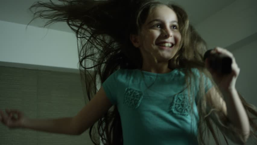 Cute little girl jumping, singing and dreaming on the bed in bedroom.  Shot on RED EPIC DRAGON Cinema Camera in Slow Motion. | Shutterstock HD Video #27253795