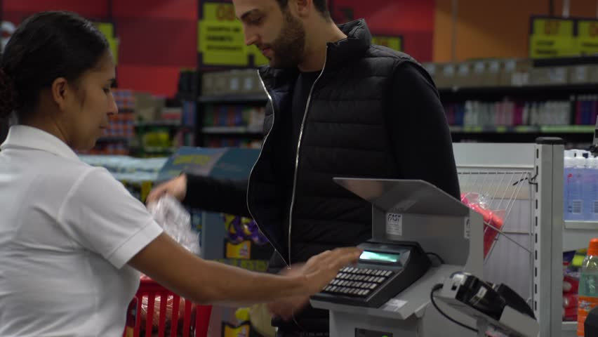 Young Customer in a Checkout Point in Supermarket #27262735