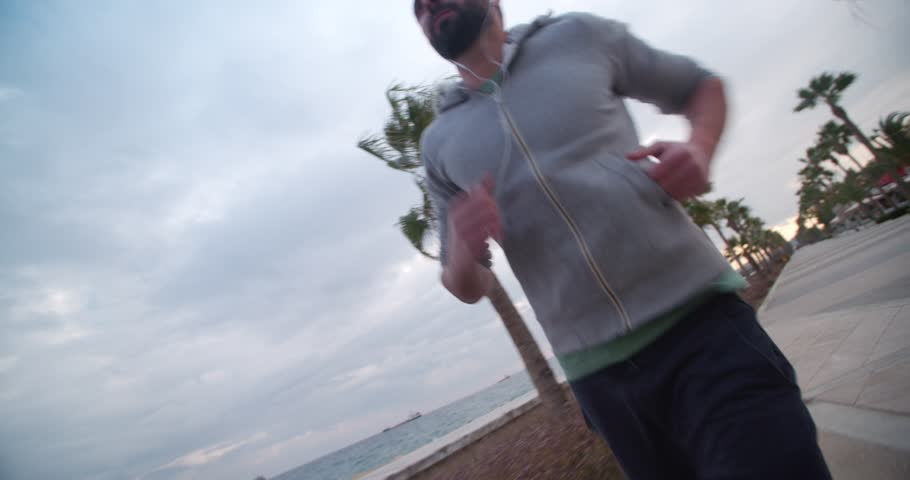 Young man in sports clothing jogging and listening to a podcast on a palm-tree beach