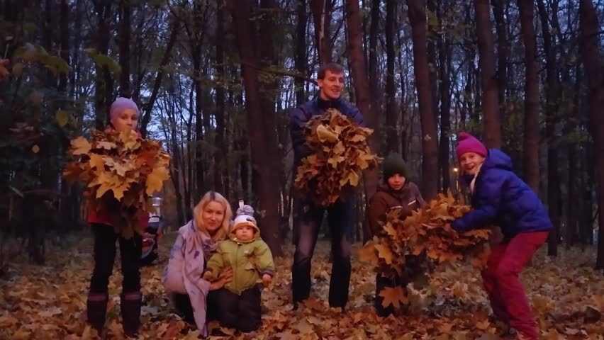 Six adults and children simultaneously throw up bunches of dry leaf in evening autumn forest, mobile phone video.