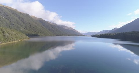 Aerial footage above a lake surrounded by trees in New Zealand. 4K