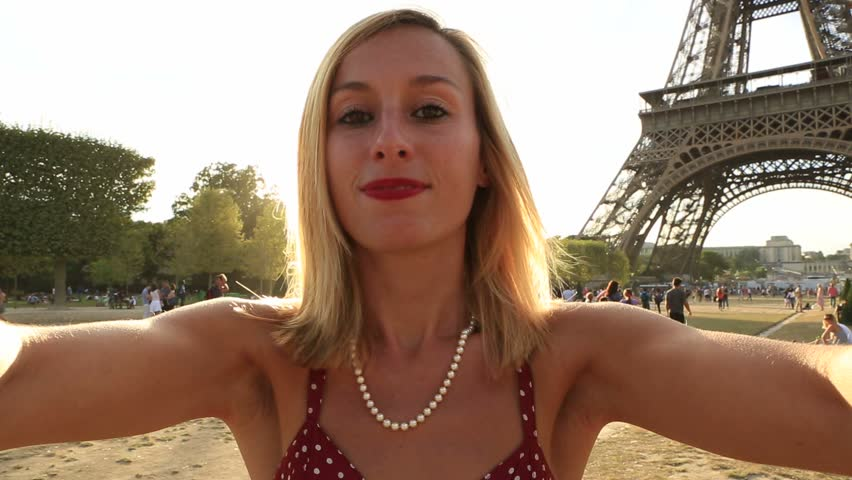 Young woman takes selfie portrait at the Eiffel Tower in France. Summer, Day, POV of woman taking self portrait by the Eiffel Tower at sunset | Shutterstock HD Video #27301615