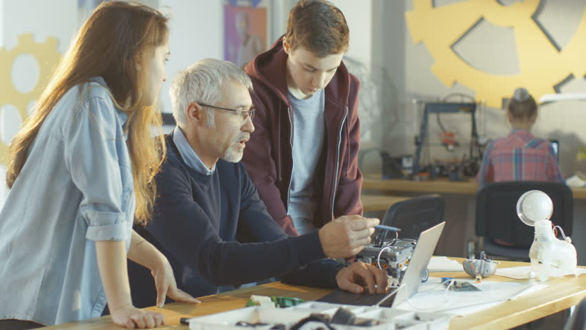 In Computer Science Class Teacher Examines programed Robot Made by Girl and Boy. Shot on RED EPIC-W 8K Helium Cinema Camera. | Shutterstock HD Video #27304615