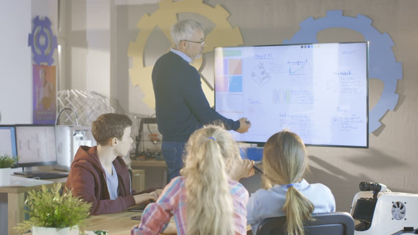 Teacher Explains Lesson To His Computer Science Class. He uses Interactive Whiteboard. Shot on RED EPIC-W 8K Helium Cinema Camera. | Shutterstock HD Video #27304657
