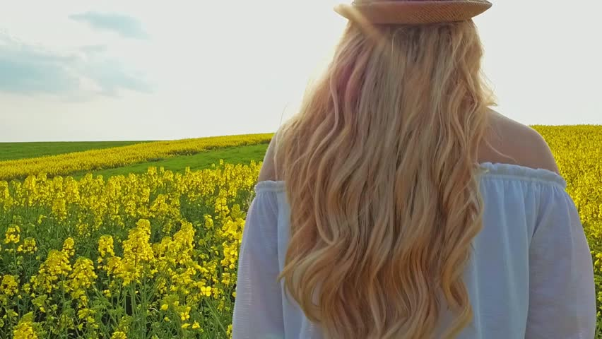 Happy woman with long hair and hat running on yellow field touching flowers | Shutterstock HD Video #27310015