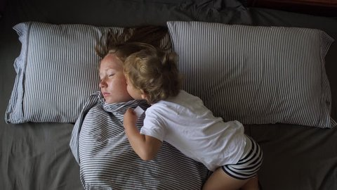 Cute little boy waking up his mother in the morning by kissing her. Flat lay medium shot