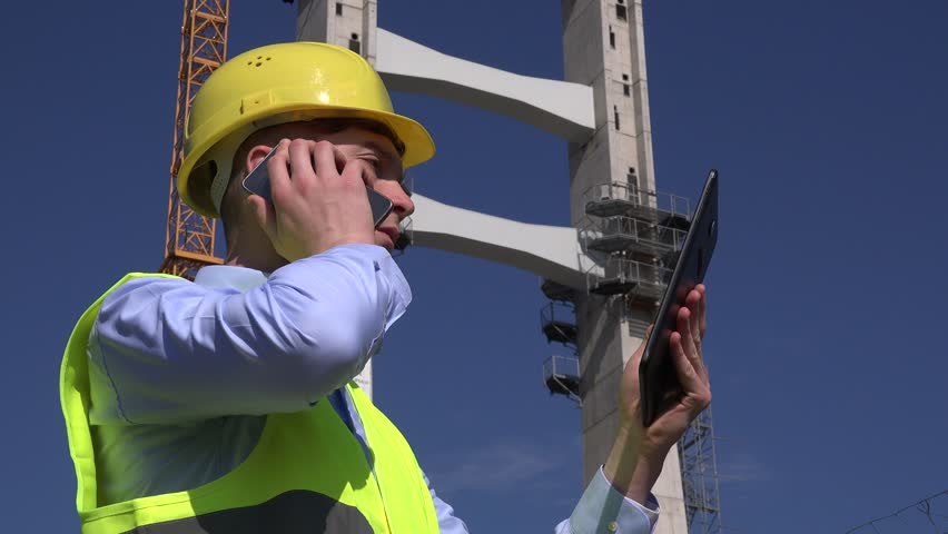 Busy Foreman Businessman Outdoors Talking To Client On Mobile Phone With A  Slide Tablet.