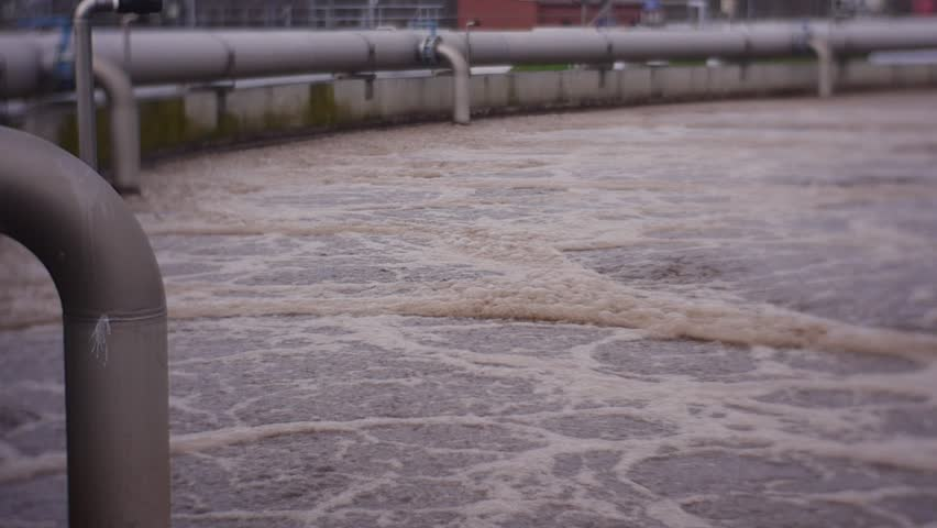 A Lot of Dirty Boiling Water in the Pool For Filtration in the Street, Cloudy, Gray, Brown Water, Urban Treatment Facilities, Water is Foaming From Bacteria and the Processes of Decomposition of Mud,