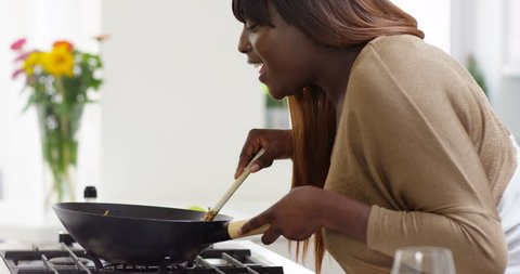 4K Happy carefree plus size woman singing & dancing while cooking a meal at home. Slow motion.