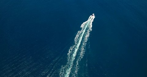 Aerial drone 4k cinematic footage. Flying above speeding boat on the blue sea.