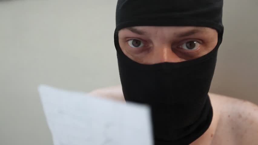 Naked young adult man with black balaclava reads a paper.