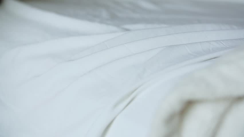 A short clip of a woman's hand smoothing over a white bed sheet to tidy it. Shot in slow motion.
