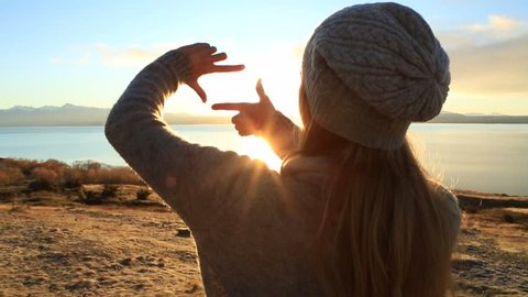 Young woman by the lake makes frame shape finger at sunrise. Woman loving nature  by the lake in New Zealand, early morning framing the sun