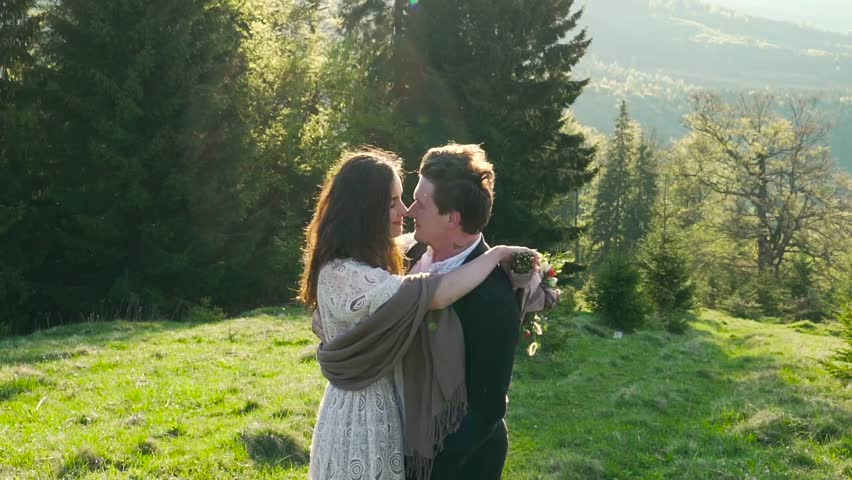 Couple is hugging on the mountains and forest background. #27425095