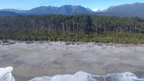 Aerial view of Bruce Bay beach, forest and distant Southern Alps, New Zealand