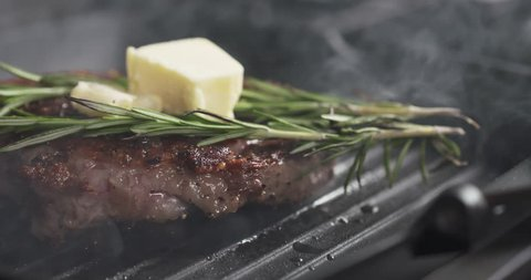 Slide slow motion shot of cooking rib eye steak with herbs and butter on top on grill pan, 4k 60fps prores footage