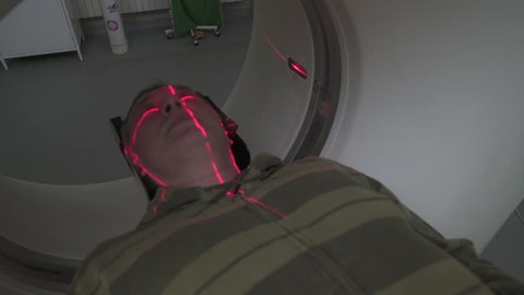 Middle aged man lying on the CT or MRI scanner during machine imaging his body, lights up infrared rays and male patient passes through the circle, crane shot from portrait to up, room interior