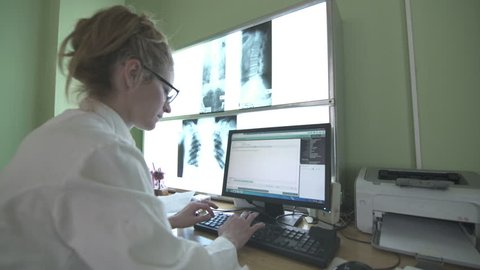 Female Caucasian radiology specialist in white coat is sitting at computer and typing on the keyboard medical results during examining x-rays on the light board, steady cam shot, wide angle lens