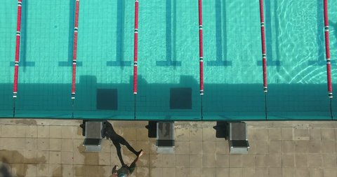 Drone bird's eye view of swimmer jumping into pool; trailing him