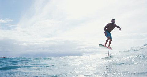 Surfer on hydrofoil surfboard riding blue ocean wave. Futuristic surfing on foil hover board.