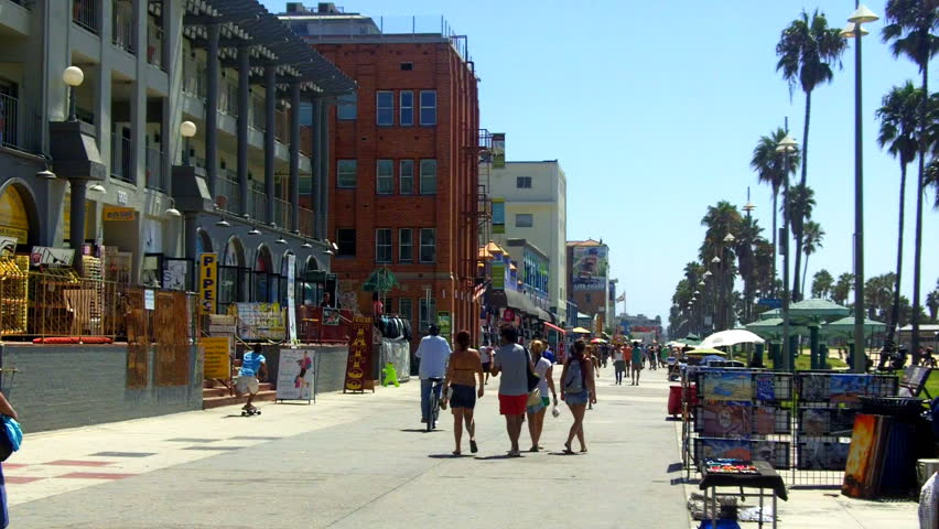 A shot looking down the Venice Beach Boardwalk with souvenir shops, historic buildings, palm trees and people walking.  | Shutterstock HD Video #2753834