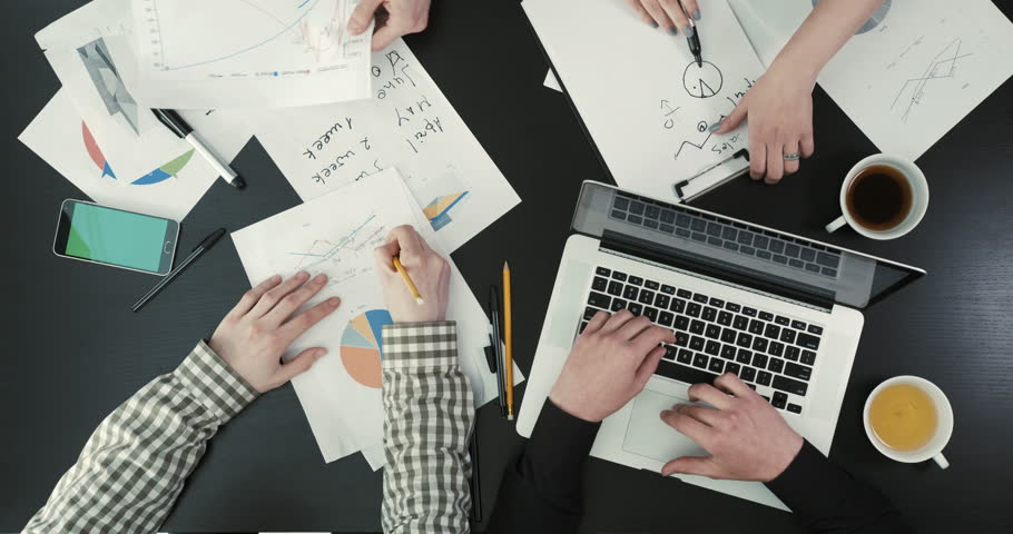 Close-up above view of the businessmen hands sorting the graphics, writing and typing on the laptop. The business composition. | Shutterstock HD Video #27562495