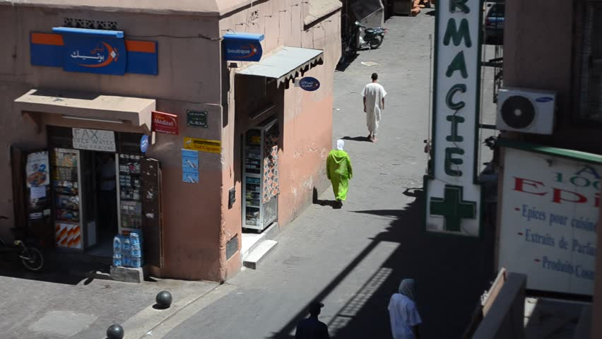 MARRAKECH, MOROCCO - CIRCA 2012: People walk in the street at midday circa July 2012 in Marrakech, Morocco.