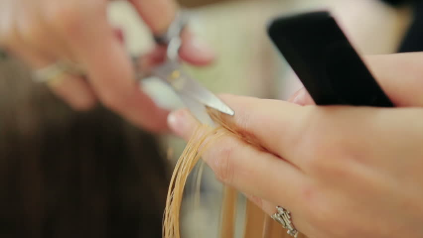 Female hairdresser hold in hand between fingers lock of hair, comb and scissors closeup. Trim the tips of the hair by scissors. stages of hair salon haircuts. wash hair before the haircut.