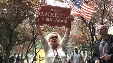 JUNE 4TH, 2017 - PORTLAND, OREGON: Woman holding sign reading Make America Great Again chants Trump Trump Trump at rally in Portland, Oregon.