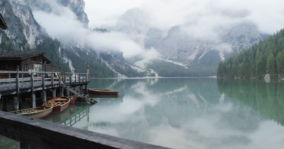 Small boathouse with wood pier and boats on Braies lake with cloudy weather.summer adventure journey in mountain nature outdoors. Travel exploring Alps, Dolomites, Italy. 4k slow motion 60p video