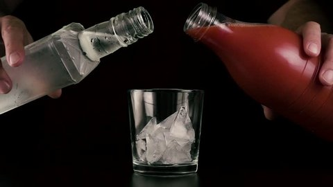 Slow motion. Male hands simultaneously pour tomato juice and vodka into a glass with ice. Cocktail bloody mary