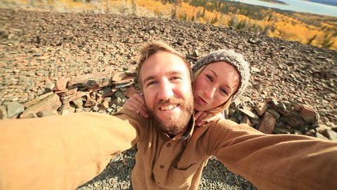 Traveling young couple taking selfie on mountain Young cheerful couple traveling in Canada takes a selfie portrait by the lake. Autumn season.