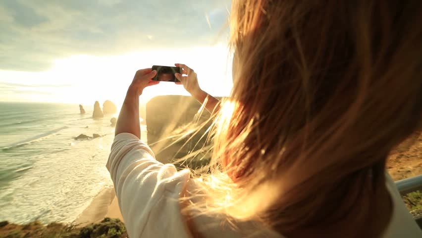 Cheerful young woman takes a picture of the Twelve Apostles sea rocks on the Great Ocean Road in Victoria's state of Australia with a mobile phone.