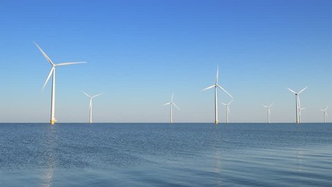 Wind turbines with turning blades in the wind in an offshore windpark.