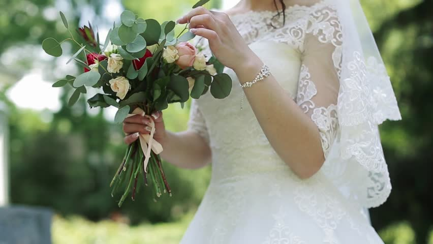 Beautiful bouquet of different colors in the hands of the bride in a white dress | Shutterstock HD Video #27645646