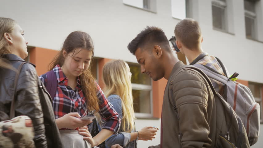 College students using their mobile phones. Diverse group of teenagers interested in their devices standing by the school. Contemporary society. | Shutterstock HD Video #27656335