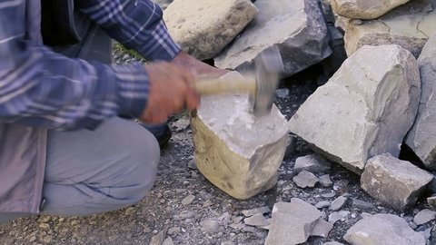 Stonemason cutting a block of granite with sledgehammer. Pitching stones for construction. Stone worker with Sledge hammer hitting concrete block. Azerbaijan Sculptor Carving Stone. Stonemason carving
