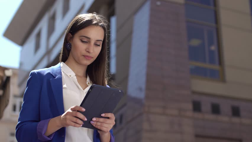 Business woman reads something on the tablet standing in the city | Shutterstock HD Video #27664765